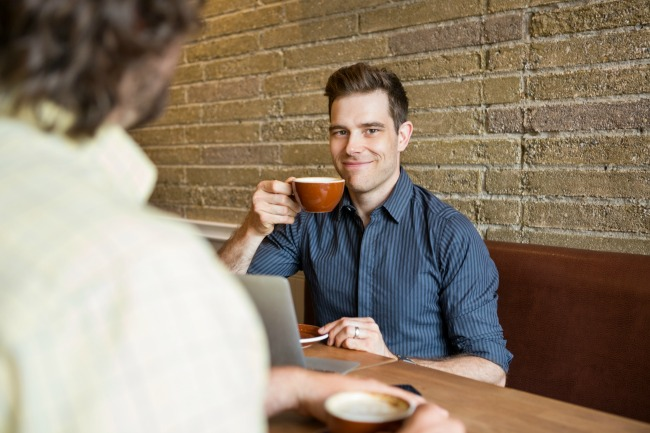 Smiling Man Having Coffee At Coffee Shop